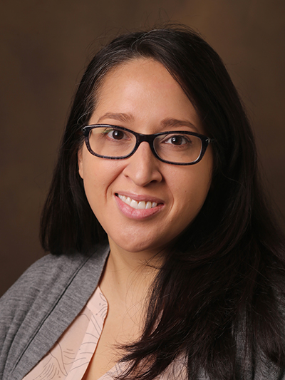 Photo of Digna Velez Edwards wearing a gray sweater and eye glasses.