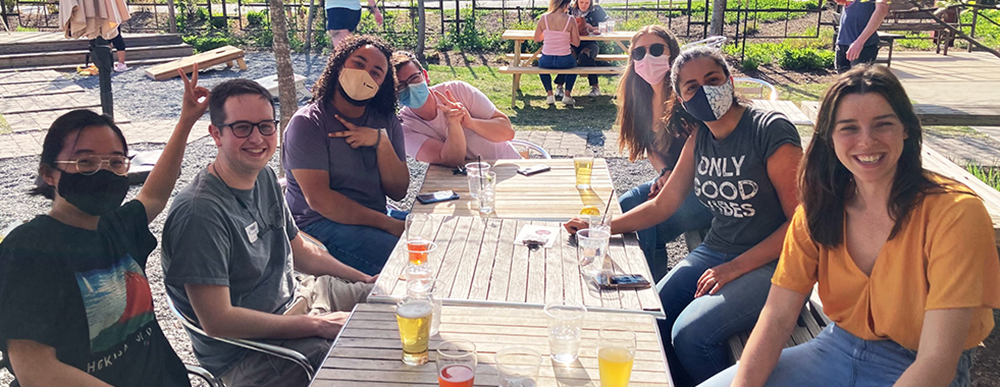 Photograph of Byndloss lab members sitting around an outdoor dining table. All but two of them are wearing face masks.