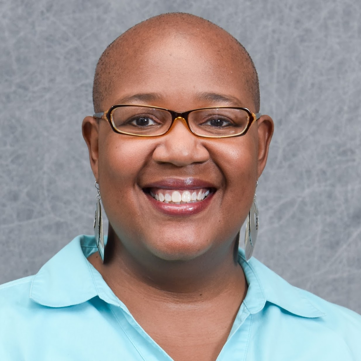 Headshot of Felysha Jenkins. She is bald and is wearing long earrings and a light-blue collared shirt.